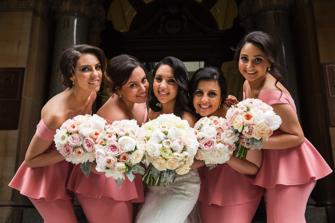 photo of a bride and her bridesmaids outside a building entrance